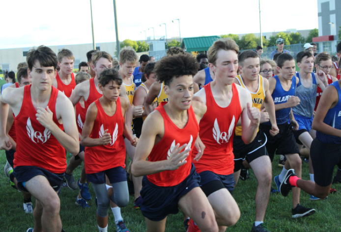 (From left to right) Sophomore Kyle Yonce, se- nior Brian Weber, senior Nathan Neumer, freshman Paul Rowden, senior Drayton Sharp, and sophomore Eliot Fyffe start off thier race at a sprint at the Olathe North Twilight Cross Country Classic Meet on September 8th.
